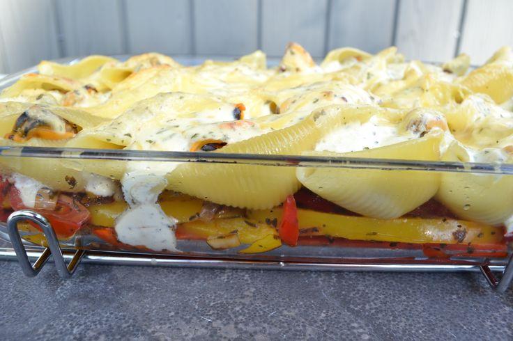 Grote pastaschelpen, gevuld met gekookte mosselen op een bedje van zoete rode paprika, gele paprika en sjalot. Bovenop ligt een kaassaus.