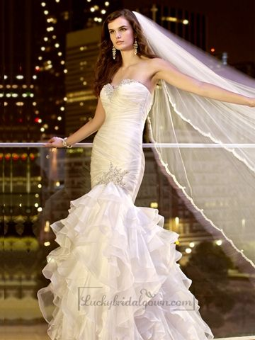 This Soft Organza trumpet wedding dress offers a draped bodice and a full skirt with dramatic layers of organza that flow full to the floor. Hand-sewn crystal and diamante beading highlight the neckline and the skirt.