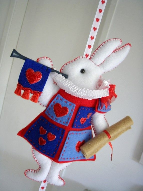 lilliputloft  --  in Australia   --  Inspired by the whimsical adventures that Alice encountered in Wonderland, this creation is hand made using felt and ribbons.  The White Rabbit is about to blow his trumpet, after reading out the song about the Knave of Hearts, to call Alice to the witness stand. Exquisitely adorable.