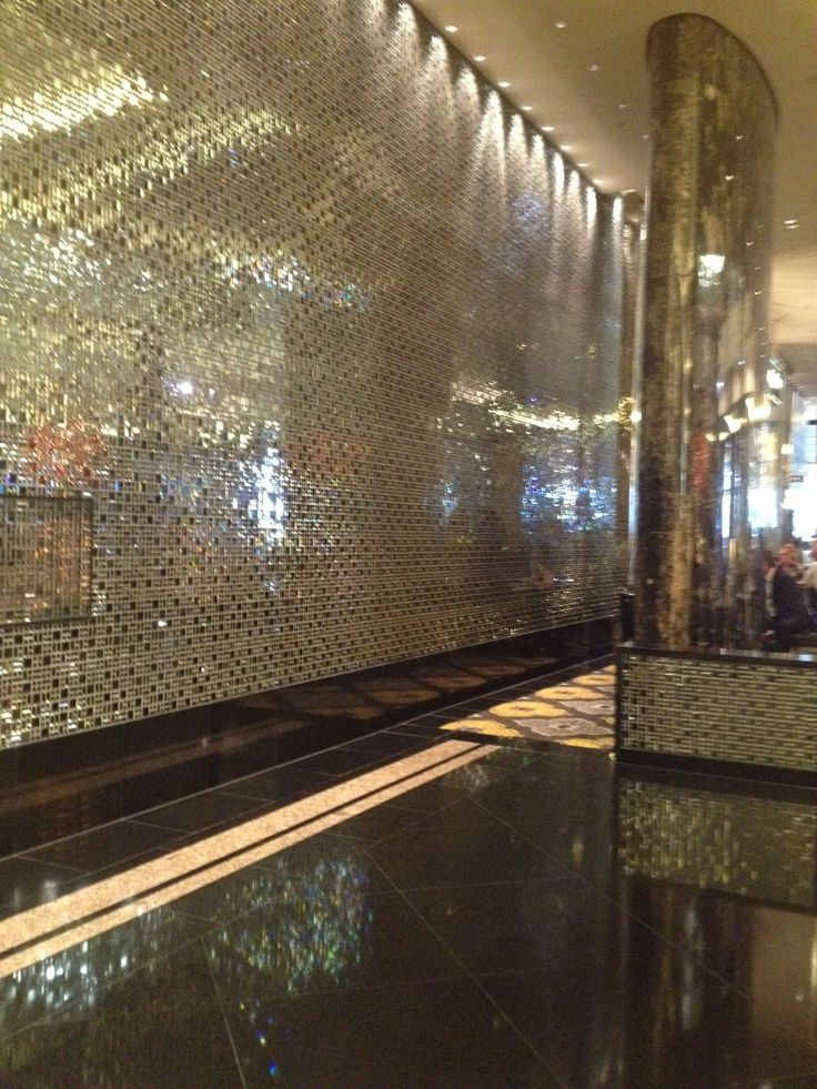 Glass and metal tiles with marble flooring.