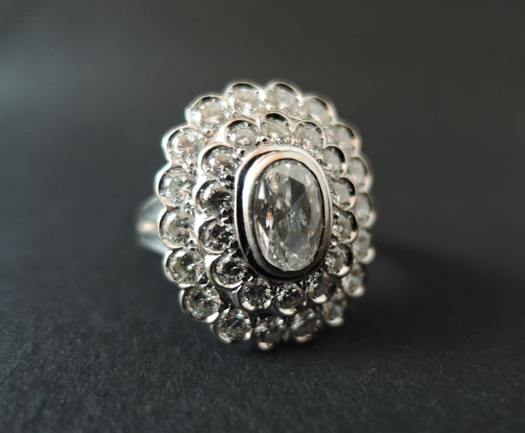 Bague en or blanc sertie d'un diamant ovale dans un double entourage de diamants taille brillant.    Or blanc 750/1000 (18 K)  Centre Diamant ovale  Poids du diamant: 0,45 carat environ  Poids des diamants: 1,10 carat environ  Poids: 7,2 grammes