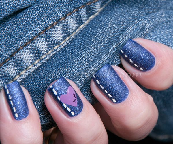 A very creative denim-themed blue nail art design. Blue glitter paint is used for the denim texture on the design. The stitch line across the design is painted in white polish with a periwinkle heart and black letter details.