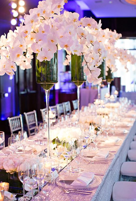 Brides.com: This Week's Best Wedding Ideas: April 11, 2014 L'Atelier Rouge provided luxurious white orchids in high green vases for a serious statement-making centerpiece. Low displays of roses and peonies, paired with glowing candles, were scattered on the tabletops.   See more photos from Rebecca and Ami's formal New York City wedding here.Photo: Lilian Haider