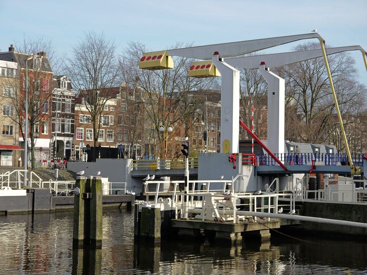 https://flic.kr/p/jzD6YG | 2014.01 - Amsterdam, photo: Modern balance-bridge architecture and old water-locks in the canal Nieuwe Vaart; a geotagged free urban picture, in public domain / Commons CCO;  city photography by Fons Heijnsbroek, The Netherlands | Amsterdam in photo: a picture of a modern foot- and bicycle bridge in front of the church Oosterkerk and the water-lock; with a view on facades along the canal-water Wittenburgergracht. The house-fronts are there a real mixture of 17th…
