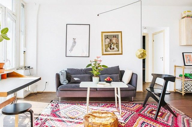 Scandinavian living space with a gray sofa and a large Persian area rug