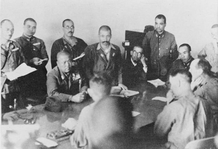Lieutenant-General Yamashita (seated, centre) thumps the table with his fist to emphasise his demand for unconditional surrender. Lieutenant-General Percival sits between his officers, his clenched hand to his mouth. (Photo from Imperial War Museum).