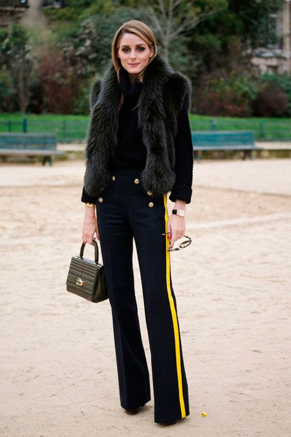 Street style look Olivia Palermo usando calça flare azul com listra amarela, blusa gola e colete de pêlo fake.