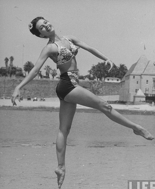 Sid Charisse striking a beautiful ballet pose on the beach during the 1940s. #vintage #beach