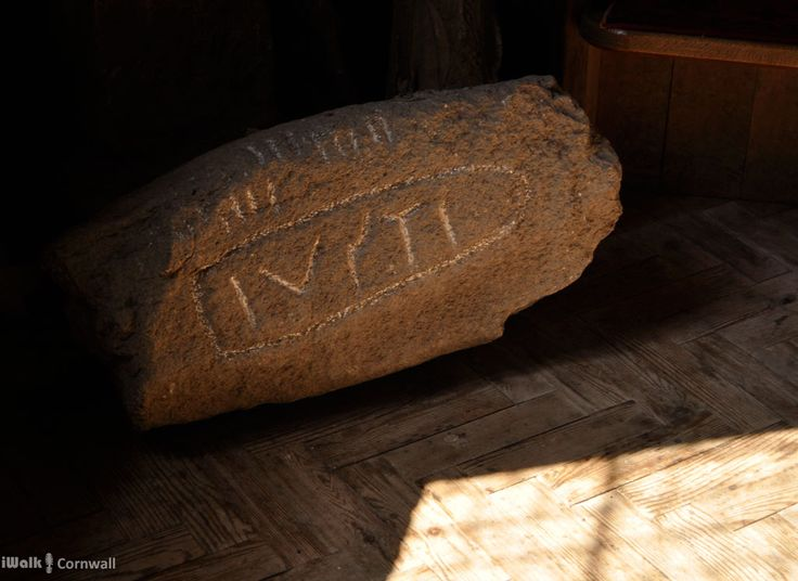 Ancient stone inscribed with Latin in the middle and Ogham (Celtic script) along the edge, in St Kew church, Cornwall.