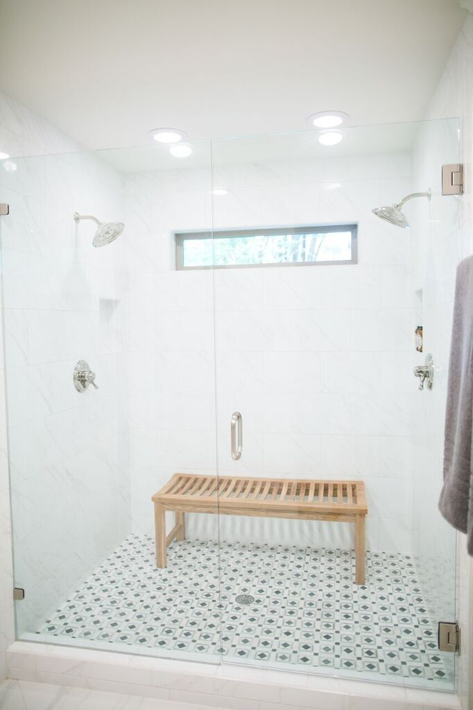 WINDOW IN SHOWER / DOUBLE SHOWER HEADS... White tiled shower, patterned tile shower base, bench in shower