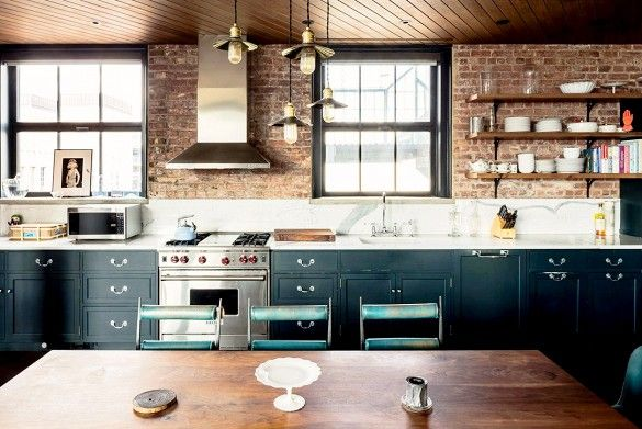 Kirsten Dunst's industrial style kitchen/ dining room features exposed brick walls and simple open shelving