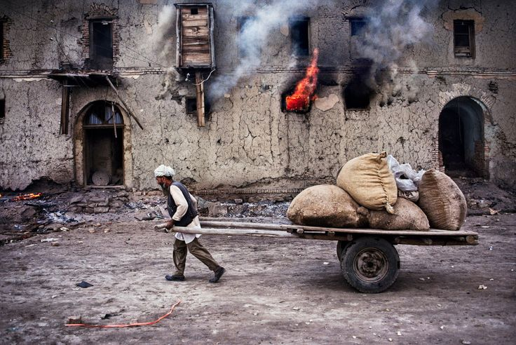 'Hazara man pulls cart past burning house', 1985. | 24 Striking Pictures Of Afghanistan By Photojournalist Steve McCurry