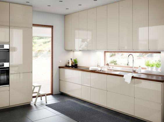 Mellomstort kjøkken med dører og skuffer i lys beige høyglans kombinert med ei benkeplate i valnøtt.
