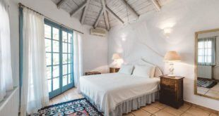 GREEK STYLE VILLAS - Double bedroom with french windows and high beamed ceilings.
