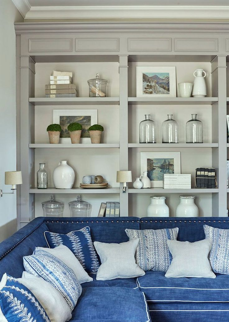 Nine Fabulous Benjamin Moore Warm Gray Paint Colors - fabulous interior design by Sims Hilditch with warm gray built in bookcases- beautifully styled and a lovely dark blue cozy sectional