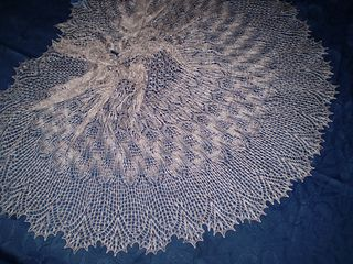 A large, heart-shaped shawl, with intricate patterning achieved through a smooth succession of simply-knit motifs.