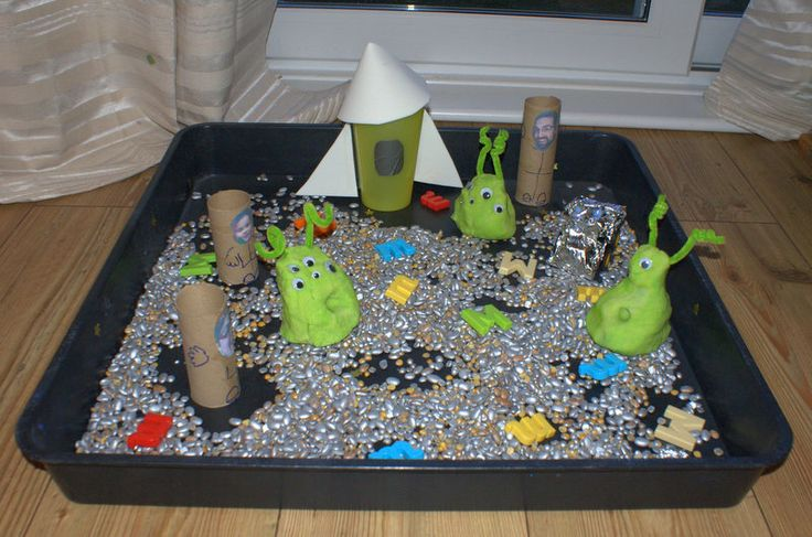 "Moonscape-  bag of split peas & a bag of beans, sprayed silver. Moon buggy - dumper truck covered in tin foil. Astronauts - printed out photos stuck on toilet rolls. Rocket - plastic cup with craft foam top & wings, duct tape windows. Playdough moon martians with, googly eyes & pipe-cleaners arms. Magnetic letters.. from Taming the Goblin ("",)"