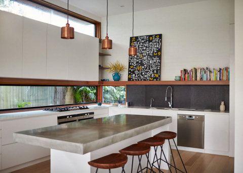No projeto do escritório Bijl Architecture, as janelas letterbox aparecem junto à bancada e acima dos armários, inundando a cozinha com luz natural.