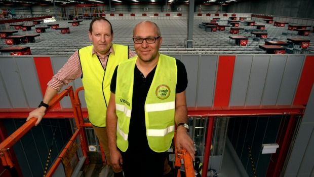 Robots Are Processing Your Catch of the Day Orders This Christmas: Catch Group head of logistics Jon Northorpe (left) and founder Gabby Leibovich on a cherry picker overseeing the company's $20 million investment in warehouse robots.