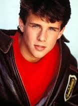 Scott Weinger wearing a leather bomber coat, and a red T-shirt.