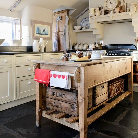 If you don't need to include appliances in your kitchen island, opt for a design that's as pretty as it is practical. This charming wooden island has a low-level open shelf for storage and display and hanging rails for drying tea towels