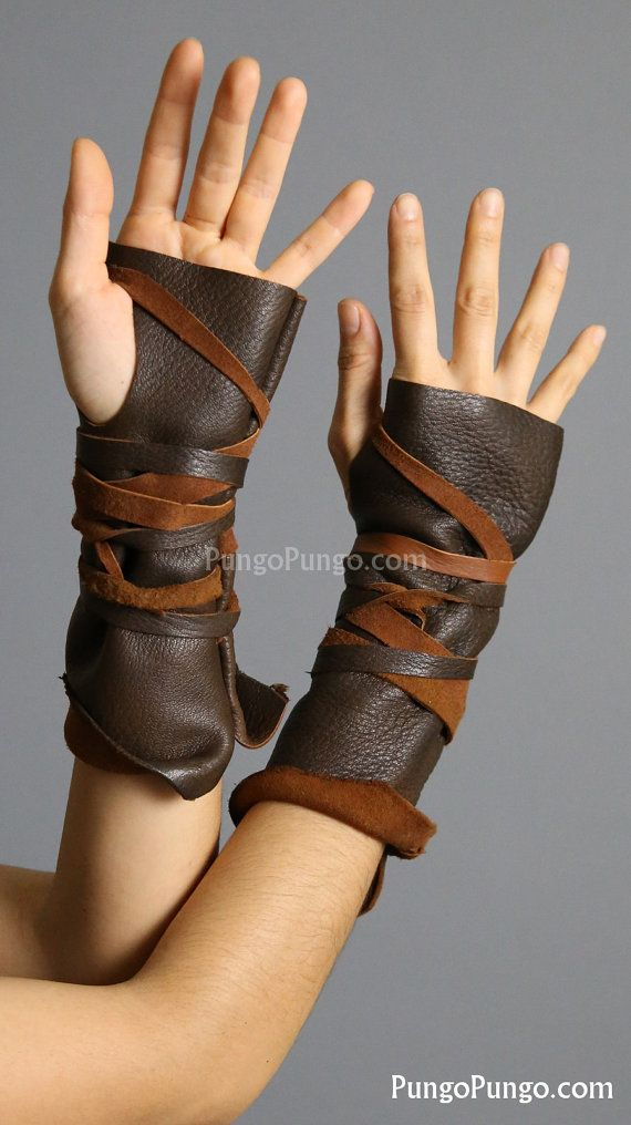 Dark Brown Fingerless Leather Gloves. Get a pair, or a single left or right hand glove!  + Handmade with dark brown, genuine leather in a slip-on style. + Overall length is about 8 - 9. + Tie strings are included to make them look wrapped and rustic! + The natural, uneven edge of the leather hide at the wrist end of the gloves lends an awesome, feral look. Try rolling them up to show the contrast between smooth grain & suede sides. + The color & texture of the leather will vary slightly…