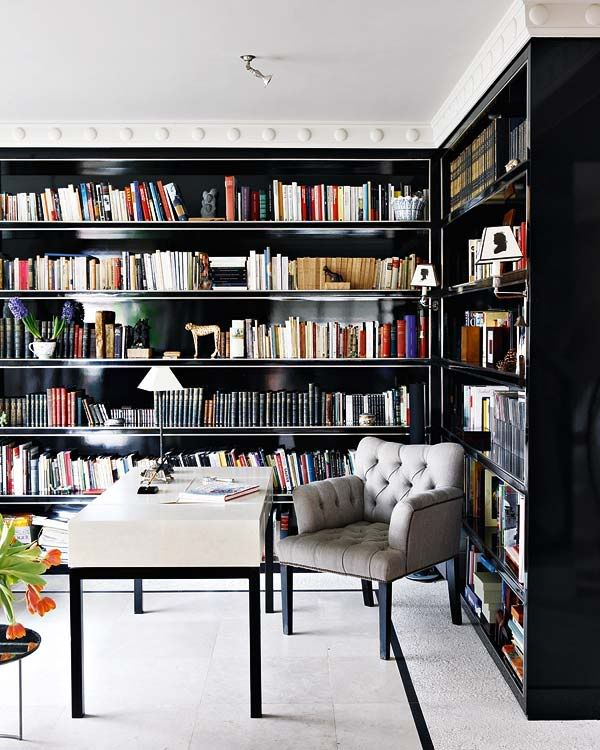 Continuous black lacquered shelves without vertical supports in the study/office