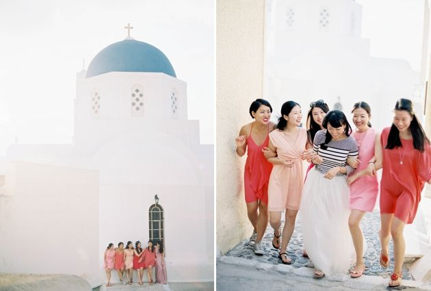 Bridesmaids being photographed with bride at a  Santorini Blue Domed Church - Stella & Moscha Exclusive Greek Island Weddings - Photo: Jen Huang