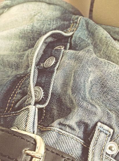 close up of denim and metal buttons.