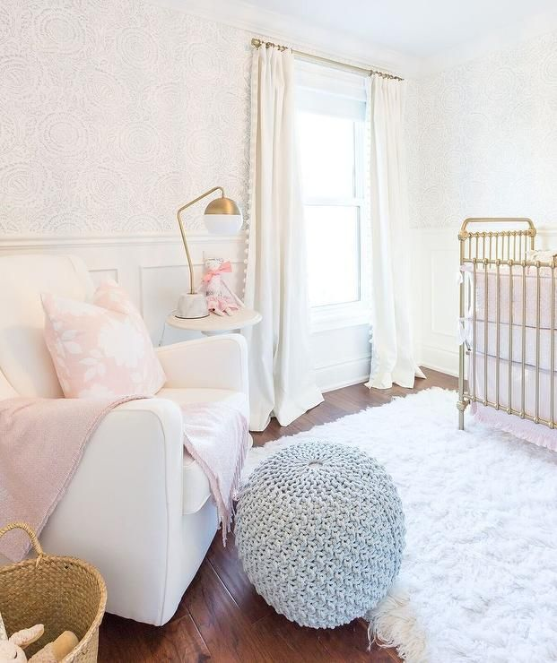 Soft girl's nursery features top half of walls clad in pale pink print wallpaper and lower half of walls clad in wainscoting lined with a vintage gold crib dressed in pink ruffled bedding.