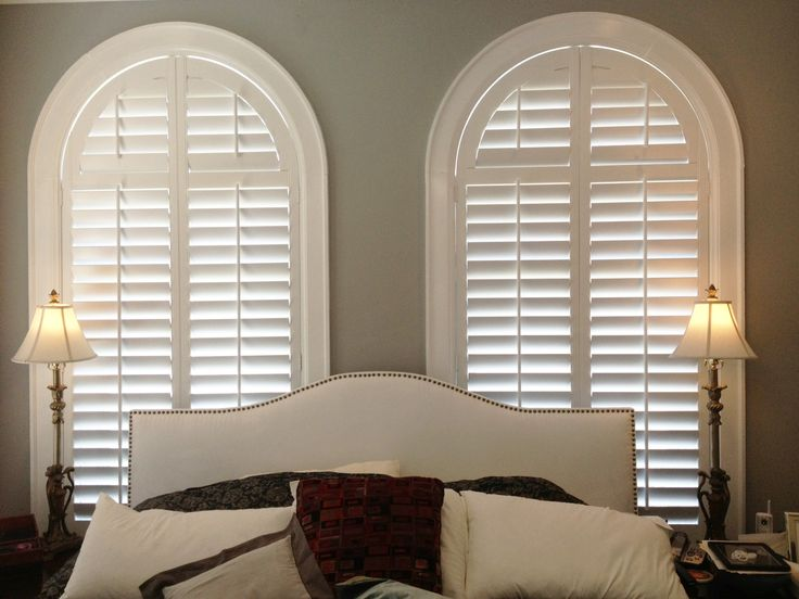 Arched plantation shutters by The Louver Shop make a great backdrop for this master bedroom.  #archedwindows #homedecor