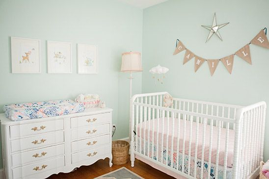 The sweet nursery combines multiple color trends: mint, coral, navy and brass. And is it just us or is that the Jenny Lind crib?