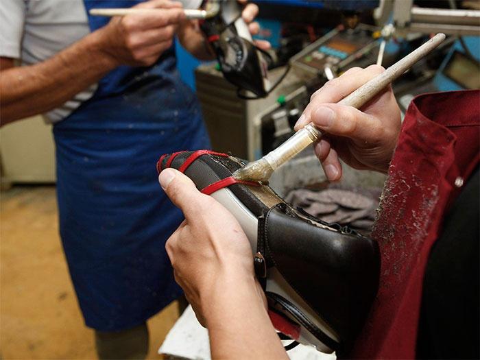 Nachdem der Unterboden angeraut wurde, wird er mit zwei verschiedenen Kleberarten bestrichen. Die Auftragung von Vor- und Hauptstrich erfolgt bei Damenschuhen von Hand, die Herrenschuhe werden maschinell bestrichen.