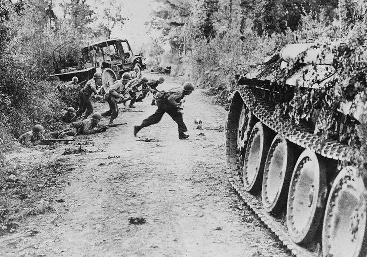 Soldados americanos corren a través de un camino de tierra que está bajo el fuego enemigo cerca Sant-Lo en Normandía- Francia- el 25 de julio de 1944