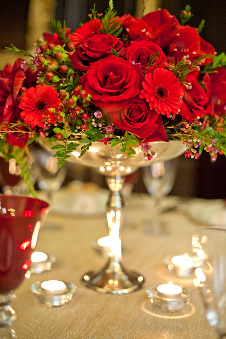 """Red centerpiece- so, a LOT of things I like about this- I wasn't sure how wax flowers would look with the red roses and hypericum berry combo I fell in love with, but they look darling! The softer, """"lime-ier"""" greens of the ferns and other greenery in this are in sharp contrast to the dark green  ivy I've envisioned, but it still looks nice. And I'm actually quite fond of the silver bowl, too"""