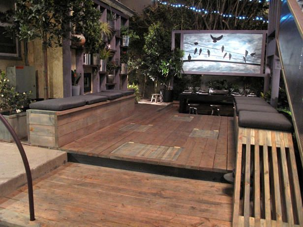 A movable outdoor movie screen, hidden seating (recliners pop up out of the floor and the benches), a sunken bar area and a wall of plants, makes maximum use out of a small space.