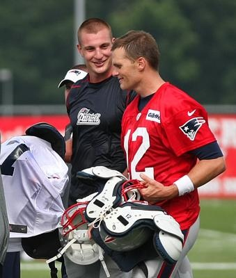 Rob Gronkowski and Tom Brady chat as they take off their pads at the end of practice.
