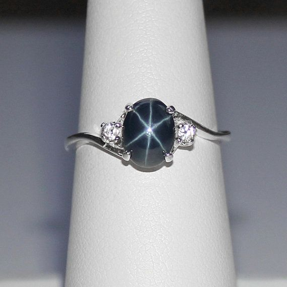 This sterling silver blue star sapphire ring showcases a genuine blue star sapphire (earth-mined in Thailand), premium high-dome cabochon, accented by two genuine white sapphires (from Madagascar). All three gemstones have a total weight (combined) of approximately 2.5 carats, so this ring is not one you will easily miss...sure to attract attention!  This amazing blue star sapphire has a nearly perfect 6-ray star, which can be observed under a single source of light or natural sunlight (the…