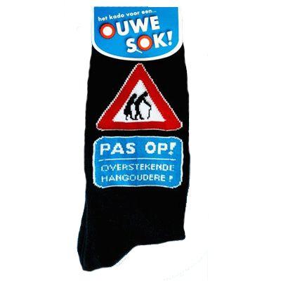 Sokken met de tekst: pas op! overstekende hangoudere! Deze grappige sokken zijn zwart met blauwe letters en met een verkeersbord waarin 2 ouderen mensen zijn afgebeeld. De sokken zijn gemaakt van: 75% polyester en 23% katoen.