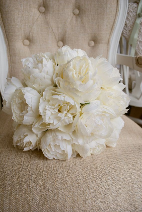 Luxury ivory peony wedding bouquet. Made with artificial peonies.  This bouquet is available in 3 approximate different sizes, - bridal (10 inch), bridesmaids (7-8inch) and flower girl (5inch). The stems of the bouquet can be bound in a satin (colour of your choosing) or ivory/white lace ribbon. This item is priced for the bridal bouquet size.  Similar items available such as buttonholes (pins/boutonnières), corsages, cake flowers and hair crowns. Extra customization to the bouquet available…
