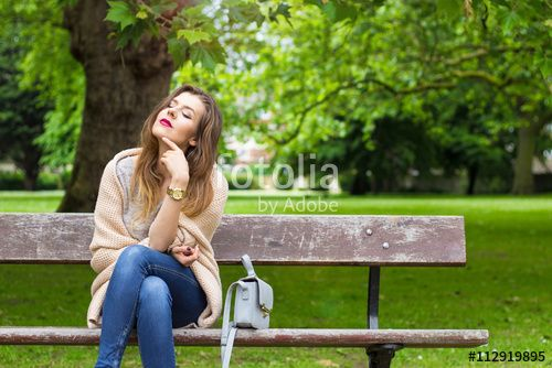 Beautiful young woman sitting on a bench in the sun and smiling