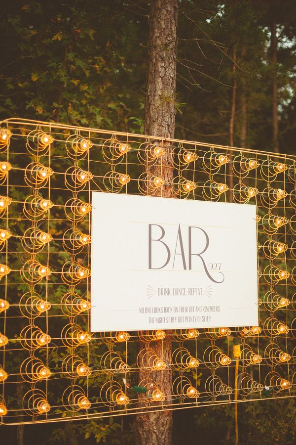 mattress spring rigged with bistro lights - photo by Kelly Maughan Photography http://ruffledblog.com/north-carolina-wedding-sourced-from-antique-shops #weddingideas #signage
