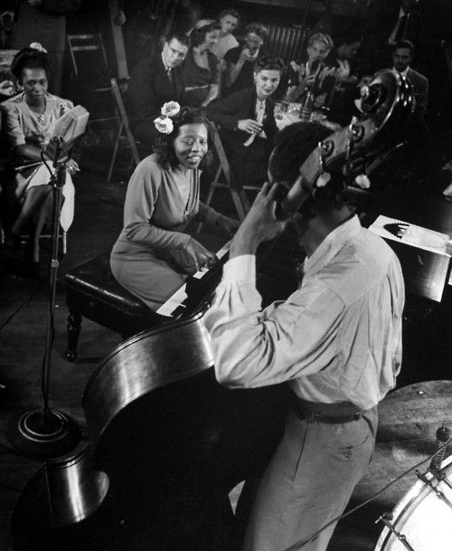 Duke Ellington, Billie Holiday, Count Basie, and other jazz greats at Gjon Mili's Studio in New York in 1940…    Pictured: The great pianist Mary Lou Williams appears satisfied with the way the night is proceeding, 1942. (Gjon Mili—Time & Life Pictures/Getty Images)