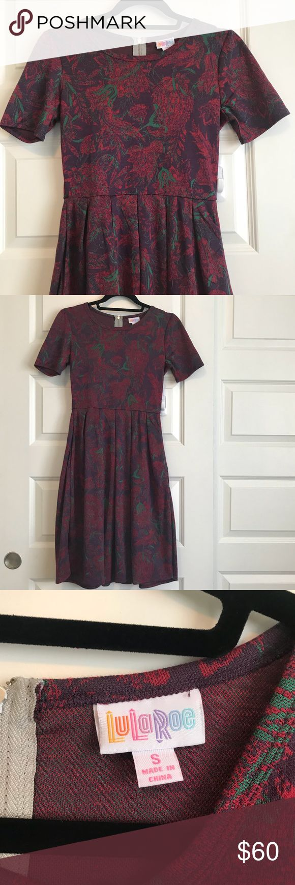 NWOT Floral JACQUARD Amelia Lularoe Purple Dress S This print is so pretty, in a lovely heavier weight stretchy jacquard, perfect for fall! Purple background with red and green floral design. Never worn, has been washed once cold/gentle and hung to dry- I purchased then realized it was very similar to another Amelia I had already 😭 Kinda went overboard!! Gorgeous exposed zipper, longer length, and functional pockets!!! Love, love, love my Amelia dresses! Happy to answer questions- check out…