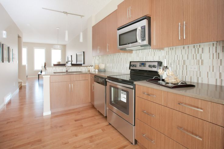 shaped kitchen with stainless steel appliances, quartz countertops ...