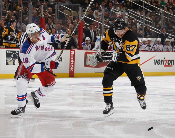 Penguins vs. Rangers - 11/15/2014 - Sidney Crosby #87 of the Pittsburgh Penguins skates for the loose puck alongside Marc Staal #18 of the New York Rangers