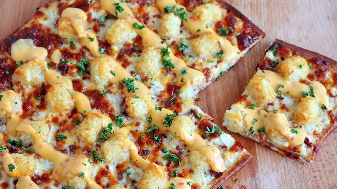 This easy loaded pizza topped with ranch dressing, cheese, bacon bits, tater tots and nacho cheese is the ultimate comfort food.
