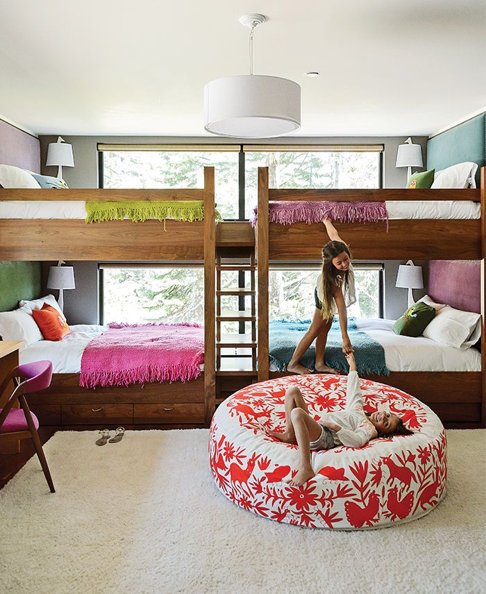 In this kids' bunk room, Maca Huneeus designed walnut beds with built-in storage and fabric headboards, and covered each one in hand-knit blankets.