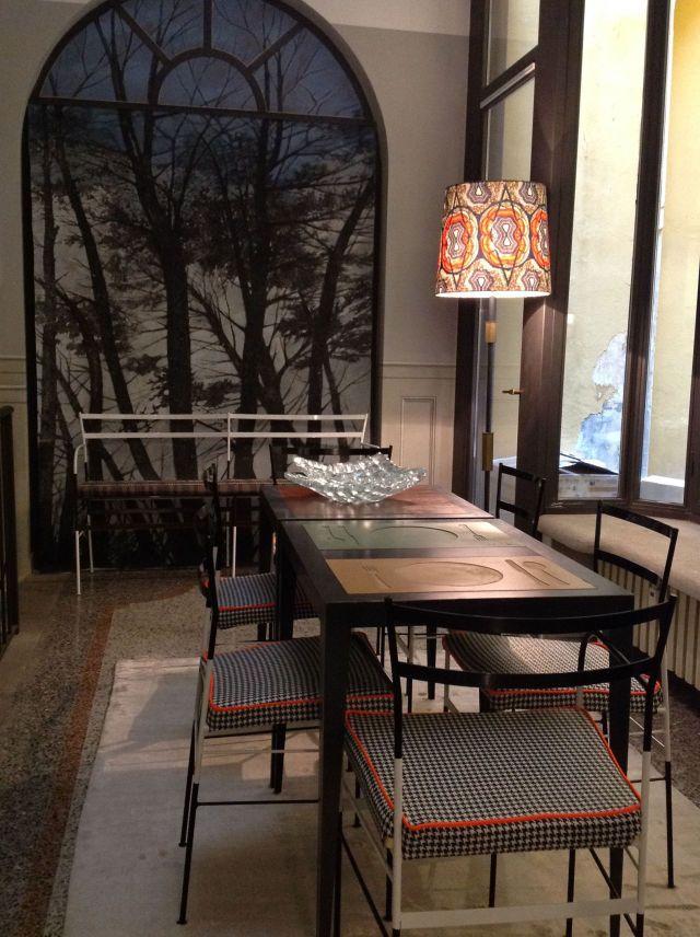 Il tavolo da pranzo con inserti colorati è di G-Lab di Davide Grosso, appoggiati sono i centrotavola in vetro di Peppino Campanella. Le sedie con cuscino e la panca sullo sfondo sono di Paolo Calcagni. Luce da terra ideata da Stella Jean