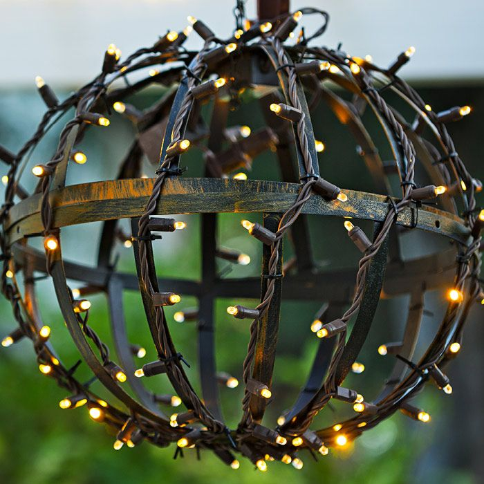 Make festive globe lights to hang from a pergola by joining two hanging baskets into a ball shape. Then wrap with string lights.